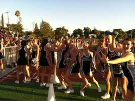The Casa Roble cheerleaders toss out mini-footballs to their supporters.