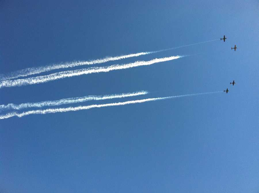 Four planes leave behind a trail of white smoke as they cruise above during the air show Sunday.
