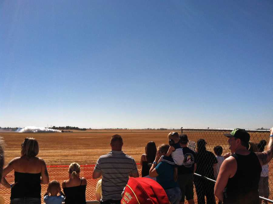 The crowd watches a vehicle rev up for a big race against a plane.