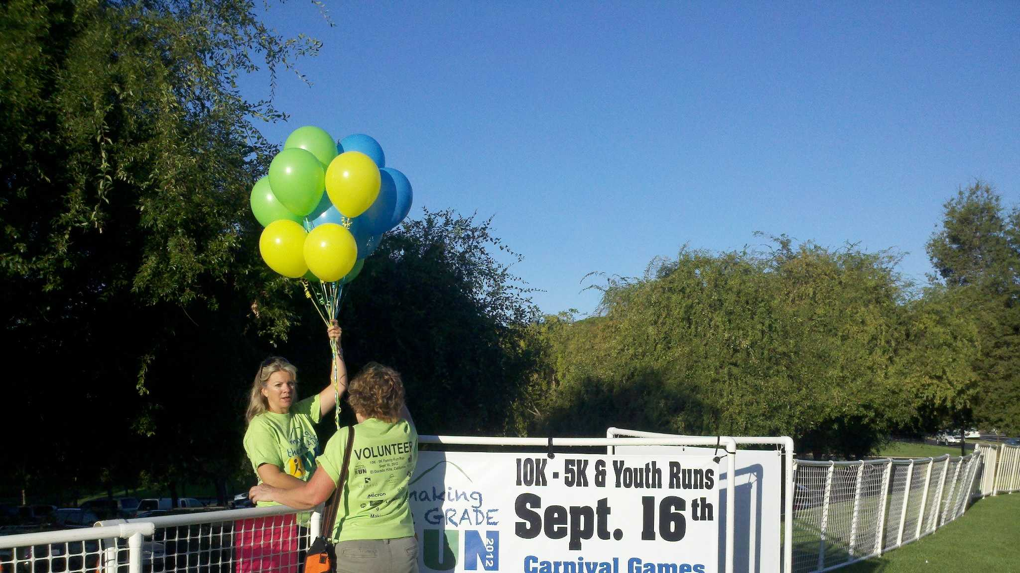 "Volunteers set-up ballons for the 2nd annual ""Making the Grade Run for Education""."