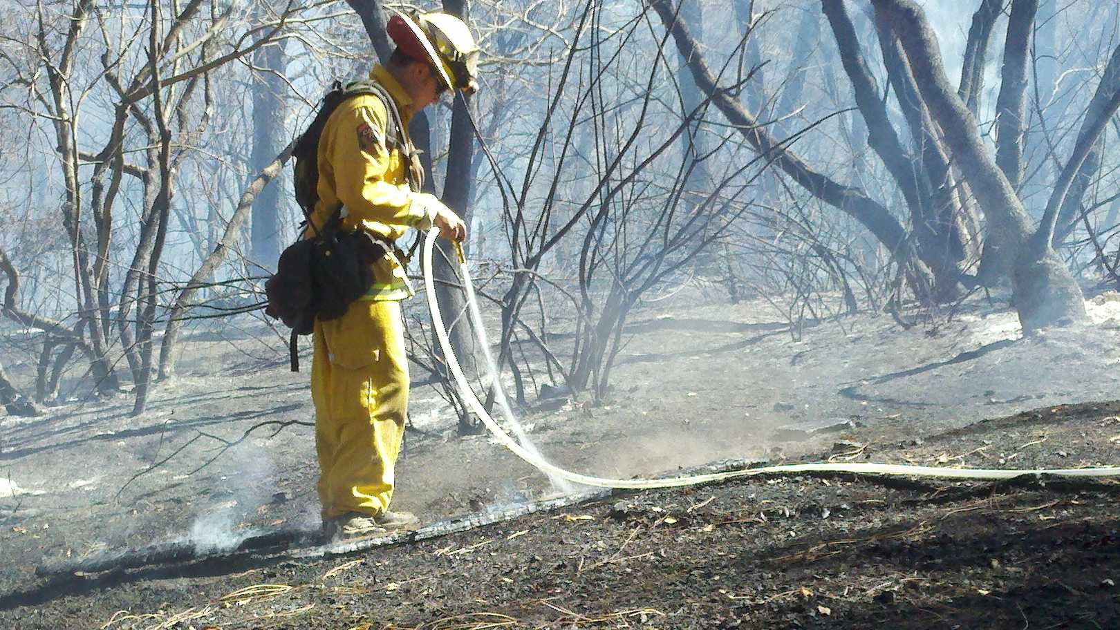 A firefighter works to extinguish a fire near Somerset on Tuesday.