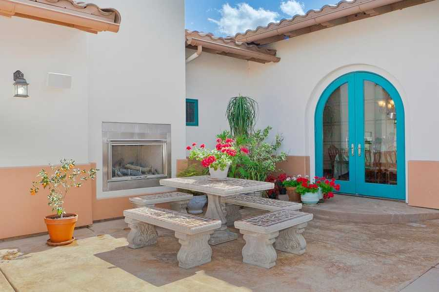 The expansive front patio has seating and dining areas and outdoor fireplace.