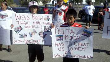 Children of the Weston Ranch Falcons hold up signs in support of youth sports in Stockton.