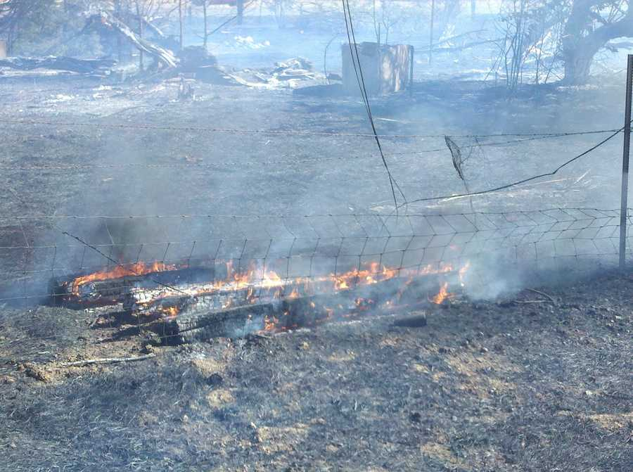 The fire charred about five acres and briefly threatened some homes.