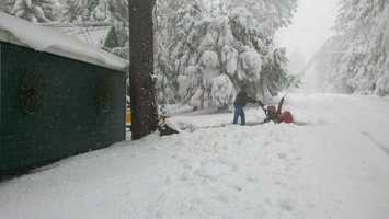 A man uses asnow-blowingmachine in the Sierra on Monday.