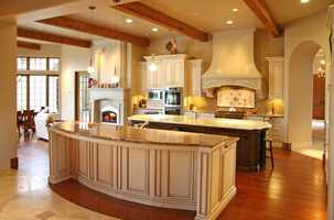 The beautiful, spacious kitchen features a marble-topped dining bar and island.
