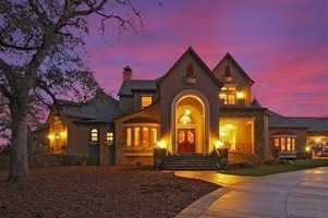 This ranch-style mansion, illuminated by the night lights, is a prime opportunity for amazing views and a charming home with ranch features inside. Listed at $4.8 million on Realtor.com.