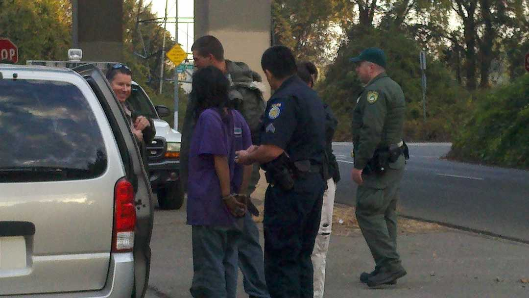 Uniformed officers detain a person found during a warrant sweep Wednesday morning.
