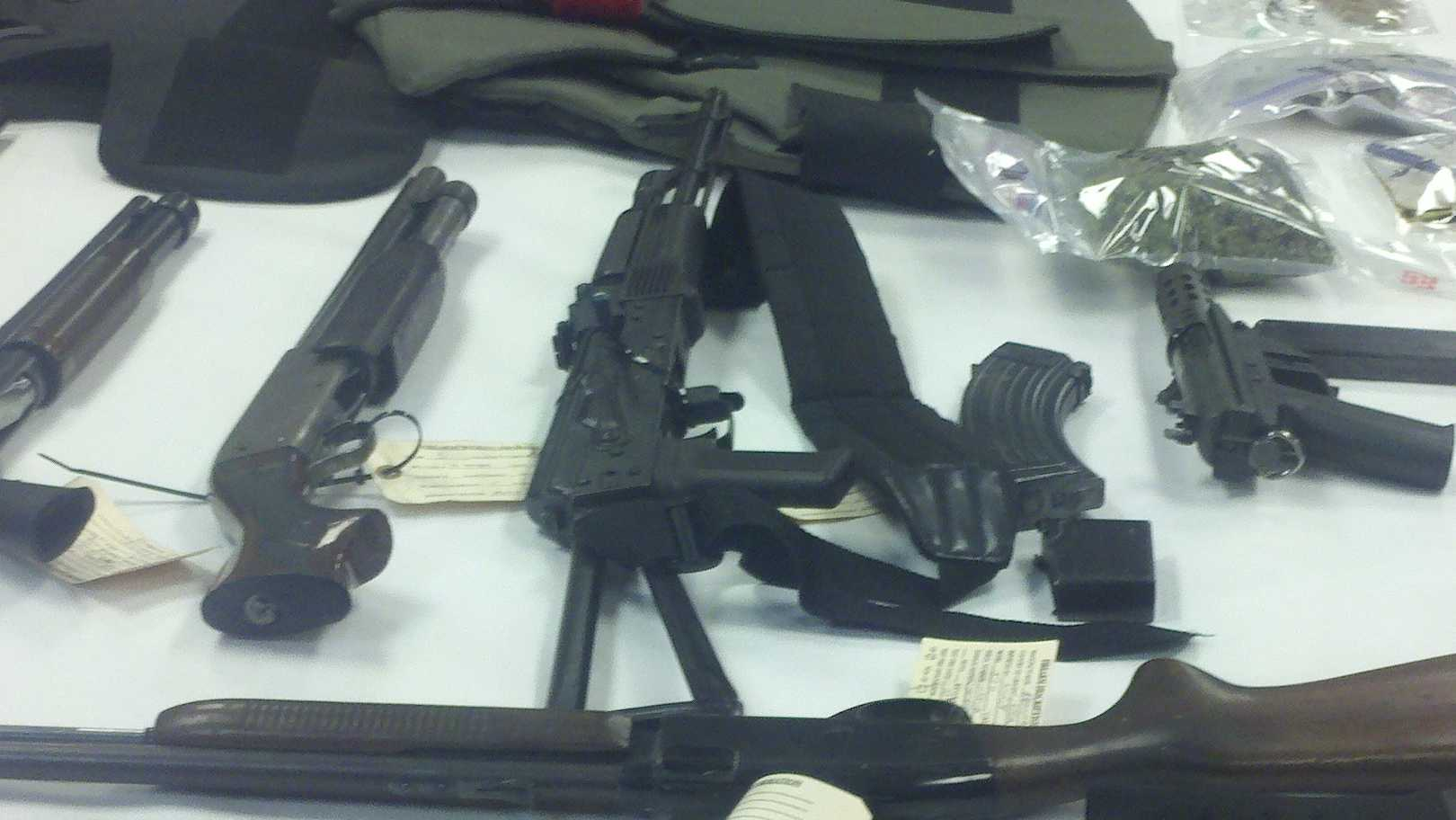 Police officers display some of the weapons they uncovered in the raids.