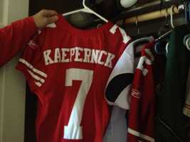 Colin Kaepernick's father holds one of his son's 49ers jerseys in Colin's room at the family's Modesto home.