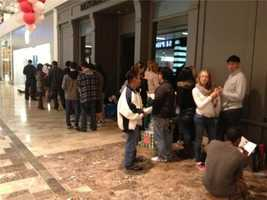 """Shoppers wait for the Apple store to open. Rumors are spreading about """"secret discounts."""""""