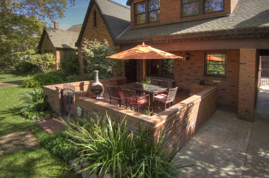 Enjoy entertaining on the front porch, which is surrounded by a handsome brick courtyard.