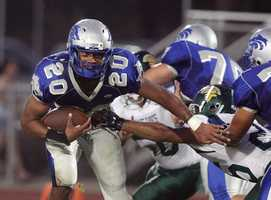 A Sierra High School football player pushes past defenders.