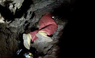 """Brian Hickey inches his way through a tunnel named """"meat grinder."""""""