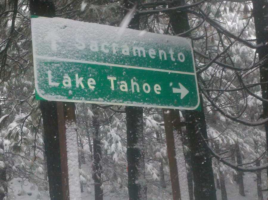 A sign on Highway 50 is covered in snow.