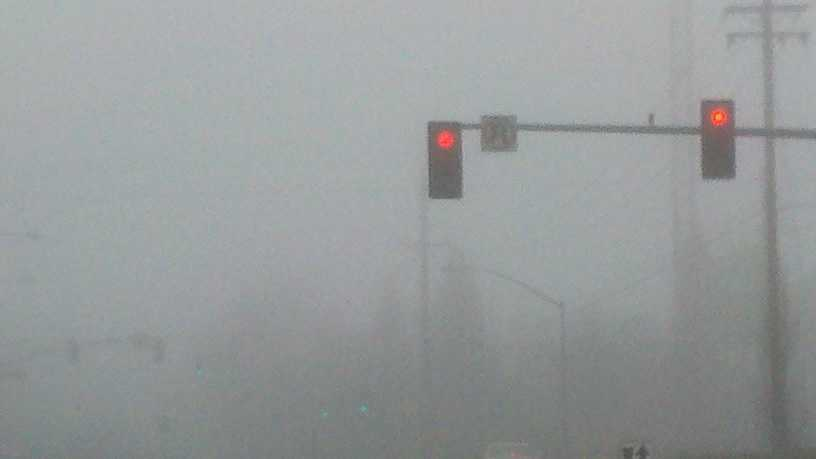 Green traffic lights are blurred by the morning fog.