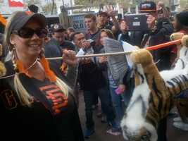 Orange-and-black clad fans begin flooding the streets of San Francisco for a Halloween Day parade celebrating the 2012 World Series champion Giants.