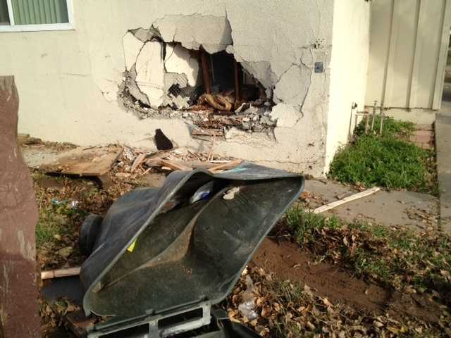 A driver who crashed into two Sacramento homes Thursday ran from the scene after leaving behind a large hole and other damage.