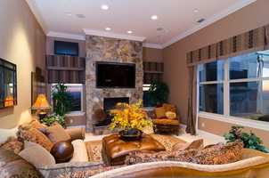 This family room has plenty of lighting and a fireplace to keep cozy.