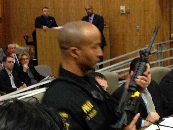 A Department of Justice member displays a semi-automatic weapon at the Capitol.