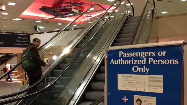 A traveler readies to pass through security inside Sacramento International Airport's Terminal A.