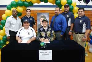John Mundt pictured with his coaches from Central Catholic on National Signing Day.