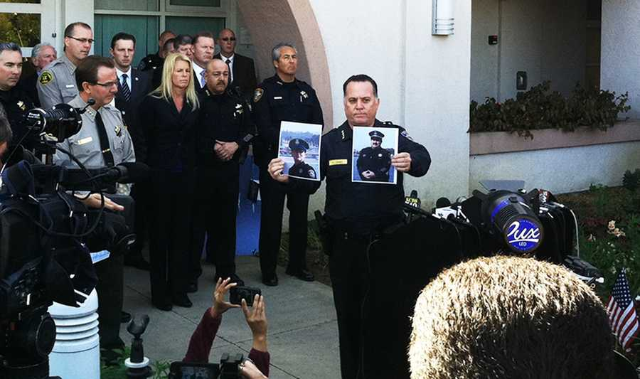 Santa Cruz Police Chief Kevin Vogel holds up photo of the fallen officers a day after they were killed. (Feb. 27, 2013)