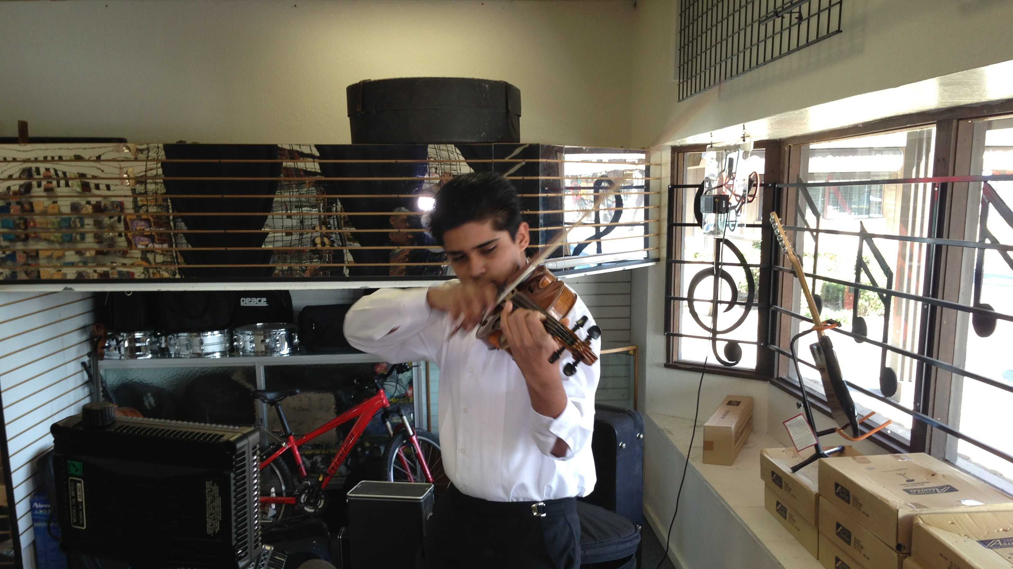 Ray Anthony Trujillo plays his violin at his father's music store in Elk Grove.