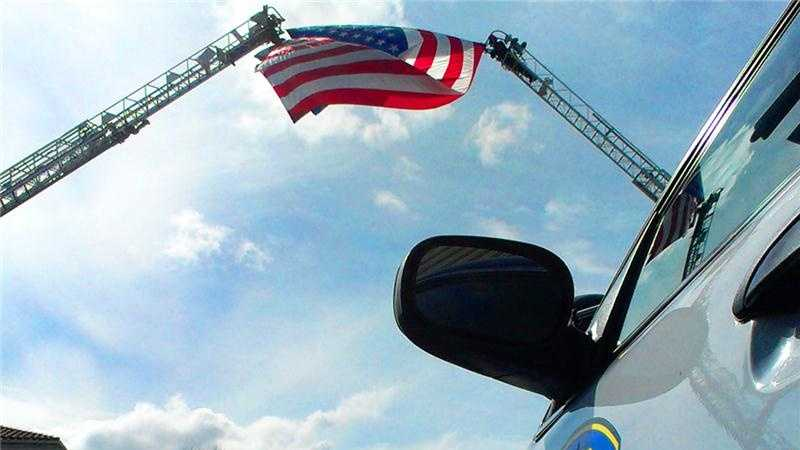 San Jose and Santa Cruz fire truck ladders holding an American flag.