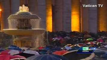 People waiting in the rain next to the Fontane di Piazza San Pietro.