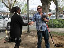 Principal Carol Brooks shakes hand with one of the men who dug up the missing elementary school time capsule.