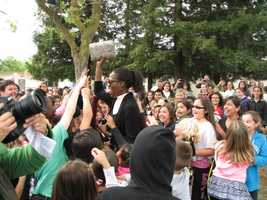 Principal Carol Brooks and her students cheer after the time capsule was dug out of the ground.