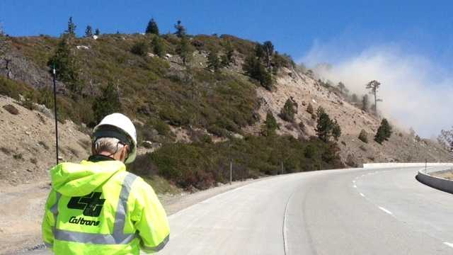 A Caltrans worker watches the intentional detonation of explosives along Interstate 80 near Yuba Gap.