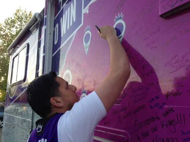 "Sacramento Kings fans sign the tour bus of ""Carmichael Dave,"" which returned from a nationwide tour and made it to Sleep Train Arena on Wednesday, for what might be the team's final home game in California's capital city (April 17, 2013)."
