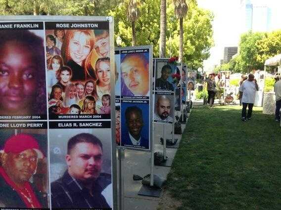 Large posters line up along the Capitol, showing the faces of crime victims.