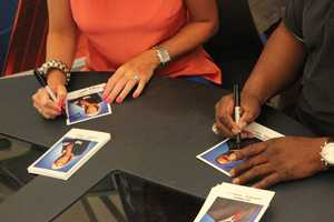 Kellie DeMarco and Del Rodgers signing autographs