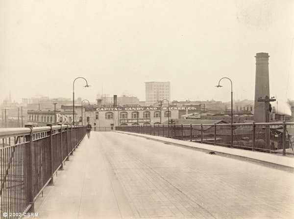 A man in the distance stands frozen in time over the Jibboom Street off-ramp of the Southern Pacific railroad bridge -- now known as the I Street Bridge.