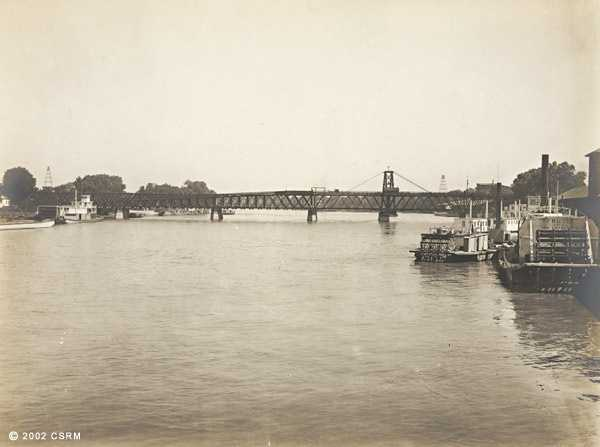 Then: In 1895, a photo is taken of the I Street bridge looking north from near J Street, but on the river, perhaps from a ship.