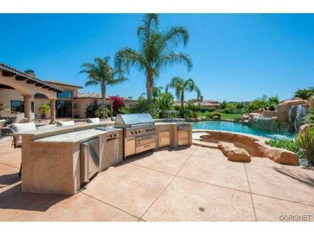 Check out that grill near the pool with slide and water feature.
