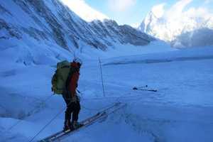 Baranov crosses a ladder bridge over a crevasse on his skis.