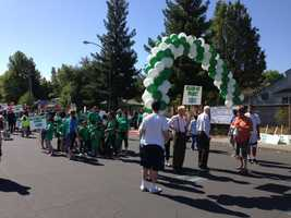 A green and white balloon arch is on display. The Loaves & Fishes Great Parade's participants to celebrate the diversity of Sacramento's homeless community.