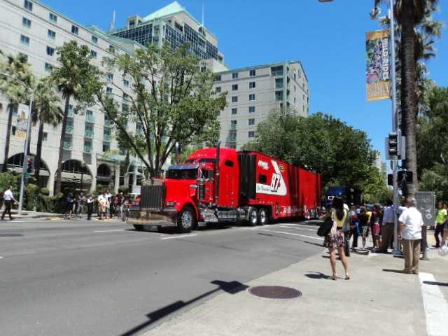Joe Nemechek's bright red hauler rolls by the state Capitol.