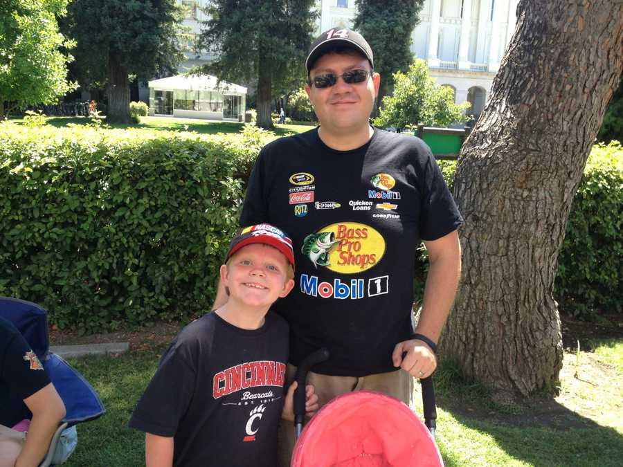 This NASCAR father-son duo find a hangout spot in front of the Capitol to catch a glimpse of the haulers with their family.