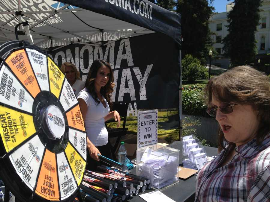 A NASCAR fan spins the wheel and wins a free Sonoma Raceway poster in front of the capitol before the Hauler Parade.
