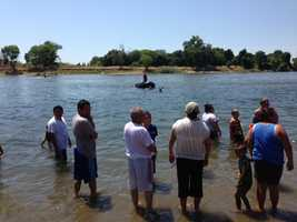 Swimmers watch as fire crews search for a 24-year-old man who went under water off the banks of Tiscornia Park in Sacramento.