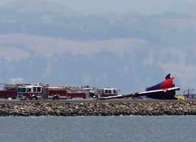 The detached tail of the Asiana Airlines plane can be seen at the end of runway 28L at SFO.