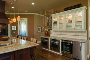 The kitchen features state-of-the-art appliances, island with sink, double ovens, beverage fridge and a walk-in pantry.