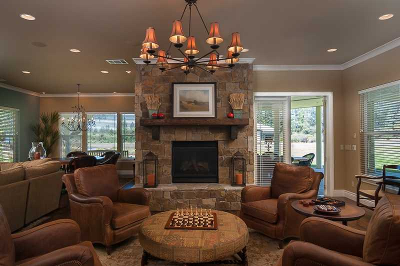 The family room features a natural stone fireplace with sweeping views and French doors that lead out to the patio area.