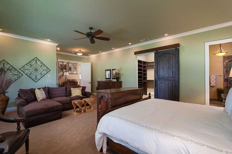 The sprawling master suite is located downstairs. It includes a sitting area and French doors that open to the covered patio.