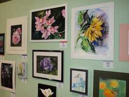 A wall full of flowers capturedby various artists in various mediums.